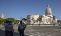 Police stand guard near the National Capitol building in Havana, Cuba, Monday, July 12, 2021, the day after protests against food shortages and high prices amid the coronavirus crisis. (AP Photo/Ismael Francisco)