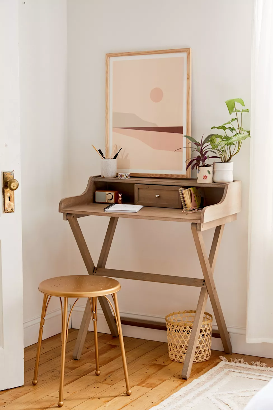 "<h3>Urban Outfitters Cory Folding Desk</h3><br>This chic-compact desk style boasts a hidden fold-up punch — meaning you can tuck this bad boy out of sight when you're not using it to be a WFH boss.<br><br><strong>Urban Outfitters</strong> Cory Folding Desk, $, available at <a href=""https://go.skimresources.com/?id=30283X879131&url=https%3A%2F%2Fwww.urbanoutfitters.com%2Fshop%2Fcory-folding-desk"" rel=""nofollow noopener"" target=""_blank"" data-ylk=""slk:Urban Outfitters"" class=""link rapid-noclick-resp"">Urban Outfitters</a>"