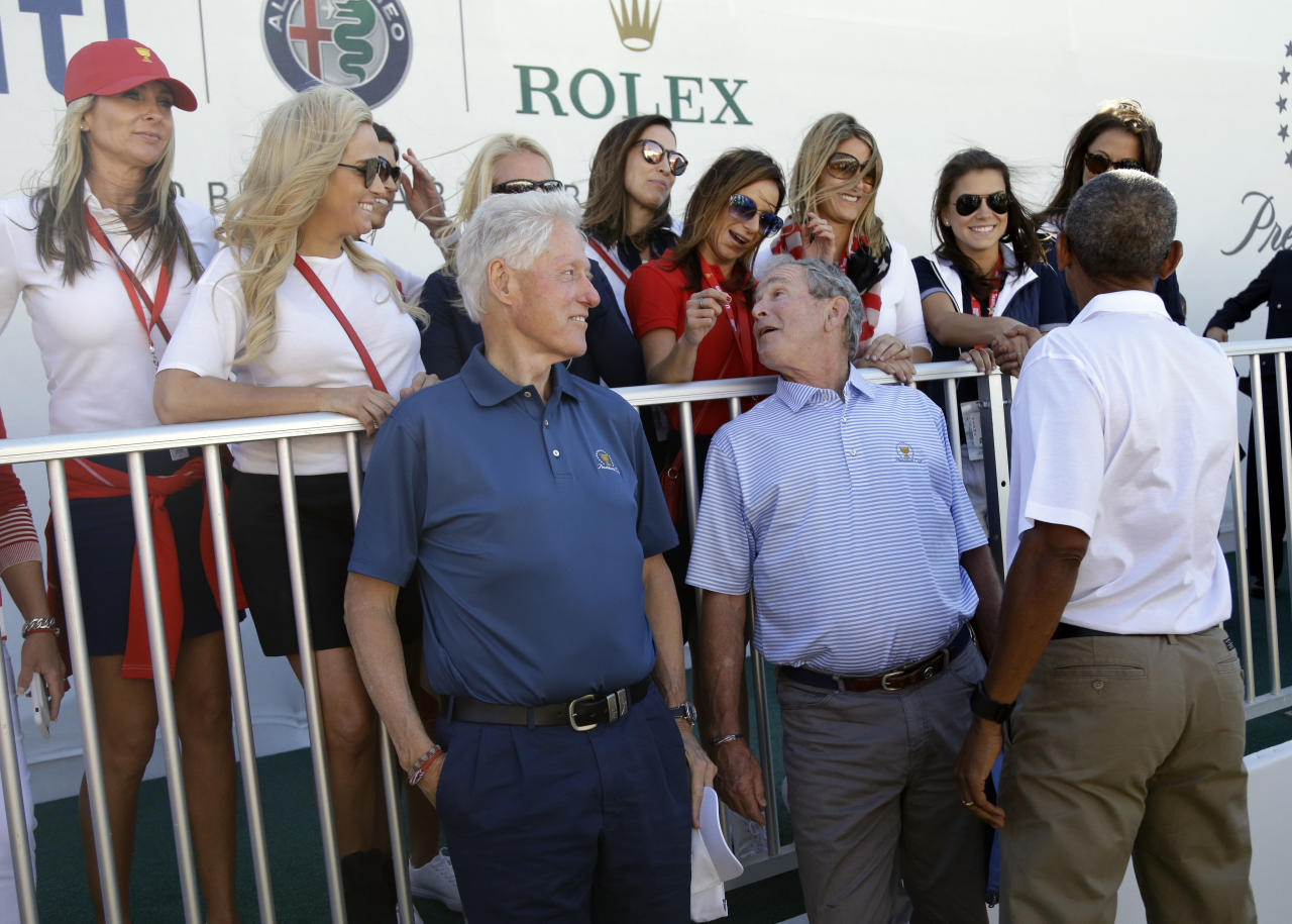 <p>Former Presidents, from left, Bill Clinton, George Bush and Barack Obama chat with wives of the U.S. team's players before the first round of the Presidents Cup at Liberty National Golf Club in Jersey City, N.J., Thursday, Sept. 28, 2017. (AP Photo/Julio Cortez) </p>