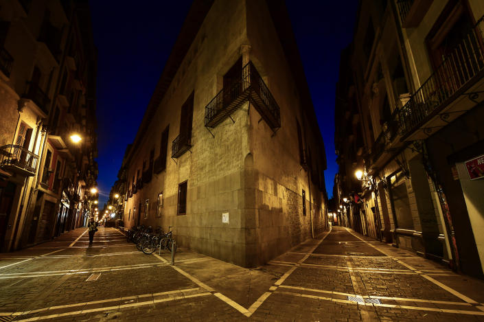 A lone pedestrian walks near to the corner between Major, left, and Jakarta street of the old city, in Pamplona, northern Spain on March 25, 2020. (Alvaro Barrientos/AP)