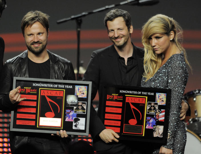 """FILE - In this April 27, 2011 file photo, songwriters Max Martin, from left, and Lukasz """"Dr. Luke"""" Gottwalk, pose with singer Kesha after receiving their awards at the 28th Annual ASCAP Pop Music Awards in Los Angeles. Gottwalk, the controversial music producer and hitmaker rose to the top of the Billboard charts with Doja Cat's ubiquitous funk-pop jam """"Say So,"""" along with Saweetie's anthemic bop """"Tap In"""" and Juice WRLD's Top 5 pop smash """"Wishing Well."""" He appeared as Tyson Trax on the Grammy ballot for Doja Cat's """"Say So,"""" which he produced and co-wrote. The hit tune is competing for record of the year, where he is contention as the song's producer. (AP Photo/Chris Pizzello, file)"""