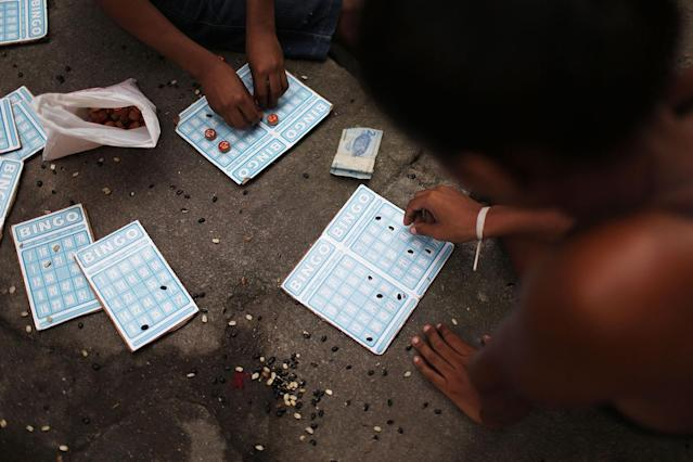 <p>Residents play bingo with beans outside a set of buildings in the Mangueira favela on May 4, 2017 in Rio de Janeiro. (Photo: Mario Tama/Getty Images) </p>