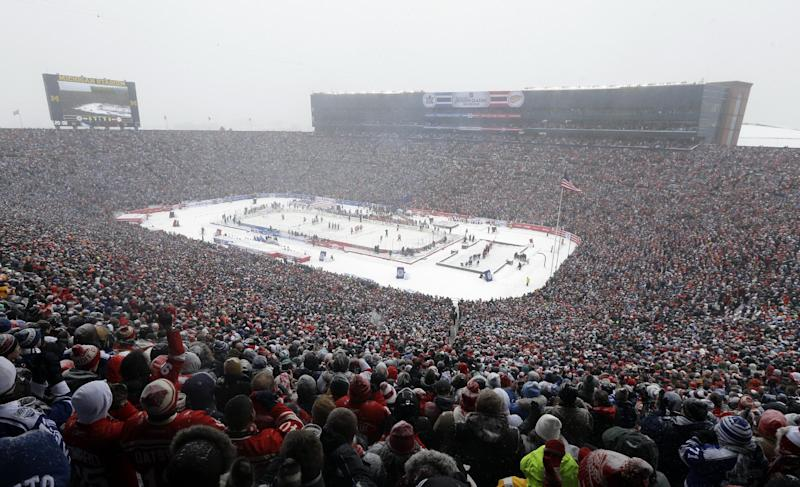 Hockey fans stand during the national anthems before the Winter Classic outdoor NHL hockey game between of the Toronto Maple Leafs and the Detroit Red Wings at Michigan Stadium in Ann Arbor, Mich., Wednesday, Jan. 1, 2014. (AP Photo/Carlos Osorio)