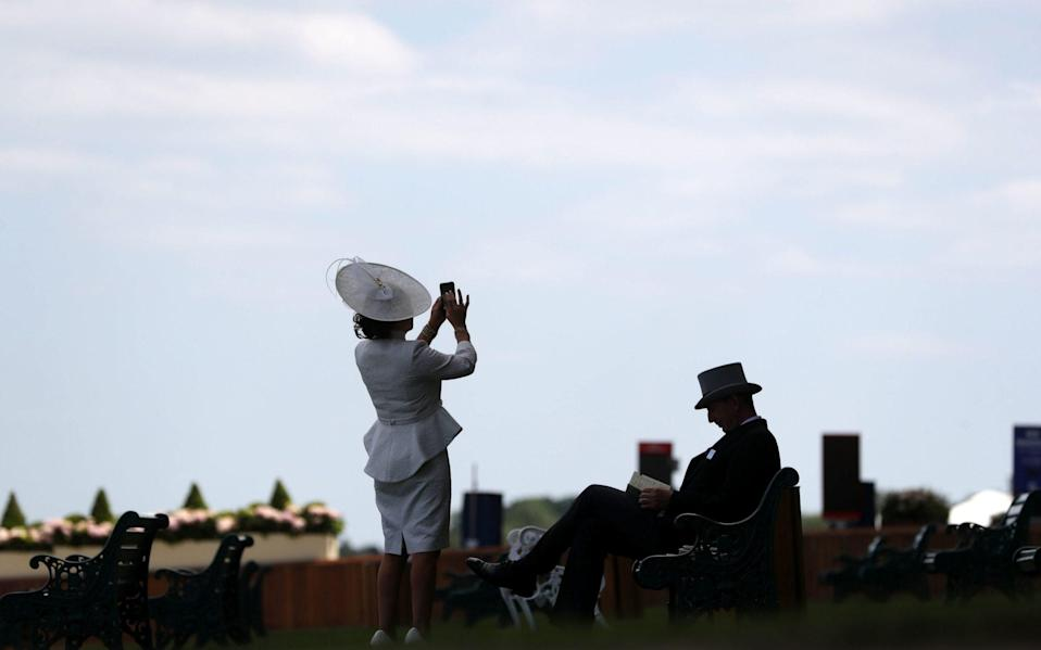 A racegoer takes a photo ahead of day two of Royal Ascot at Ascot Racecourse - PA