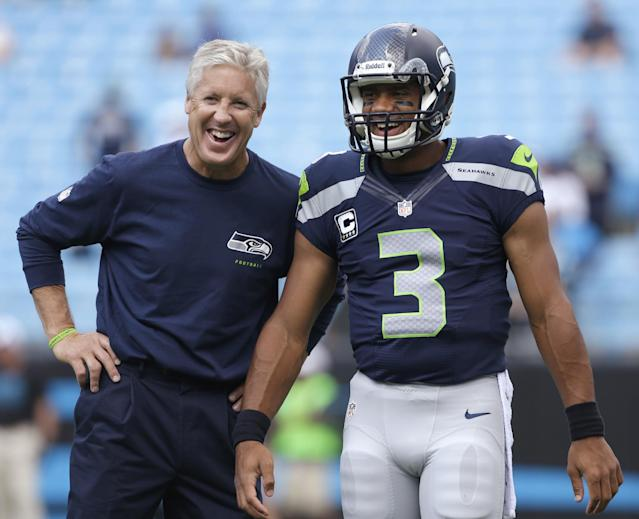 FILE - In this Sept. 8, 2013 file photo, Seattle Seahawks coach Pete Carroll, left, talks with quarterback Russell Wilson before an NFL football game against the Carolina Panthers in Charlotte, N.C. The Seahawks are scheduled to play the San Francisco 49ers on Sunday, Sept. 15, 2013. (AP Photo/Bob Leverone, file)