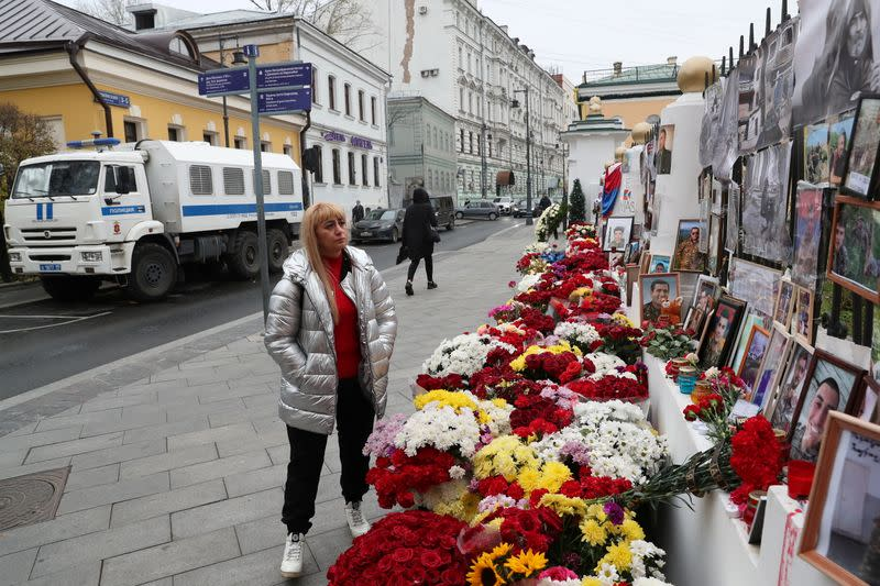 A woman stands next to a makeshift memorial outside the Armenian embassy for people killed during a military conflict over the breakaway region of Nagorno-Karabakh in Moscow