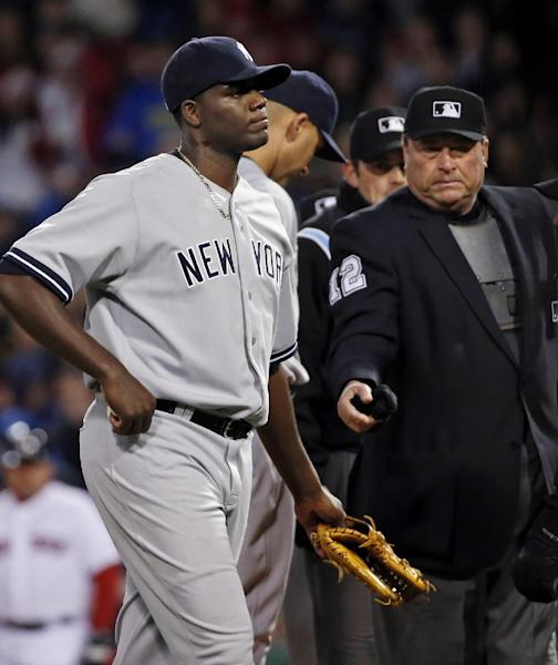 Home plate umpire Gerry Davis ejects New York Yankees starting pitcher Michael Pineda after a foreign substance was discovered on his neck in the second inning of the Yankees' baseball game against the Boston Red Sox at Fenway Park in Boston, Wednesday, April 23, 2014. (AP Photo/Elise Amendola)