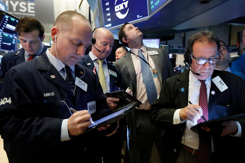 Traders gather at the post that handles Oaktree Capital Group on the floor of the New York Stock Exchange, Wednesday, March 13, 2019. U.S. stocks opened broadly higher on Wall Street Wednesday, powered by technology and health care companies, as the market pushes for its third straight day of gains. (AP Photo/Richard Drew)