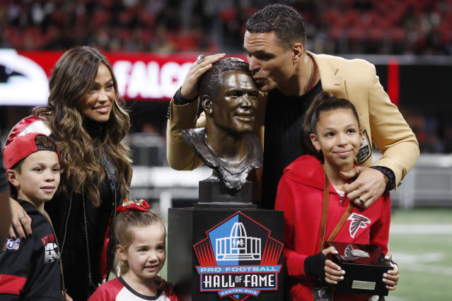 Former NFL player and Football Hall of Fame member Tony Gonzalez stands with his family as he was celebrated on the field at half time of an NFL football game between the Atlanta Falcons and the New Orleans Saints, Thursday, Nov. 28, 2019, in Atlanta. (AP Photo/John Bazemore)