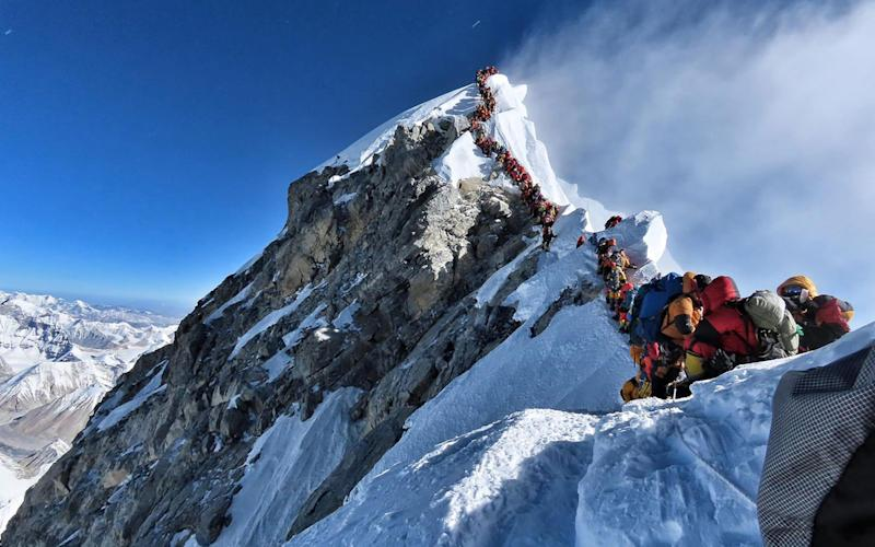 Heavy traffic of mountain climbers lining up to stand at the summit of Mount Everest in May - AFP