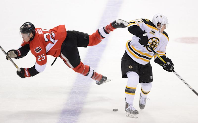 Ottawa Senators' Chris Neil, left, falls after a collision with Boston Bruins' Torey Krug during the first period of an NHL hockey game in Ottawa, Ontario on Friday, Nov. 15, 2013. (AP Photo/The Canadian Press, Sean Kilpatrick)