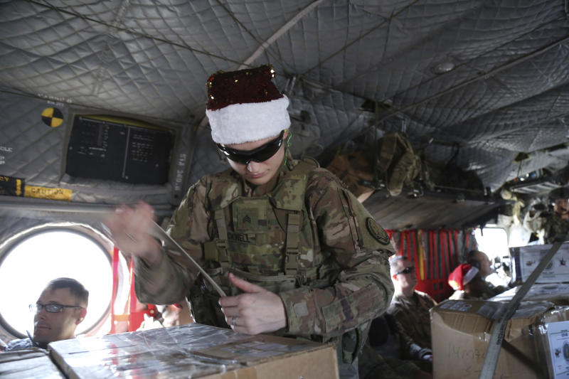 In this Monday, Dec. 23, 2019, photo, a U.S. soldier secures Christmas gifts on a helicopter in Irbil, Iraq bound for American bases in eastern Syria. It's an operation is called Holiday Express - in addition to delivering presents, the U.S.-led coalition forces brought a U.S. military band to play Christmas carols and music to several bases in eastern Syria. (AP Photo/Farid Abdul-Wahid)