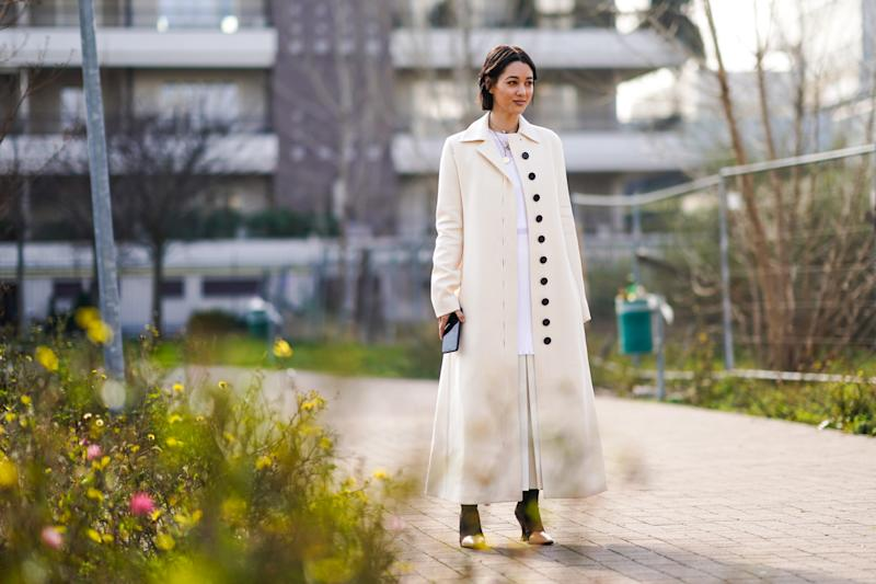 MILAN, ITALY - FEBRUARY 23: A guest wears a necklace, a white long coat with black buttons, boots with metallic parts, a white dress, outside BOSS, during Milan Fashion Week Fall/Winter 2020-2021 on February 23, 2020 in Milan, Italy. (Photo by Edward Berthelot/Getty Images)