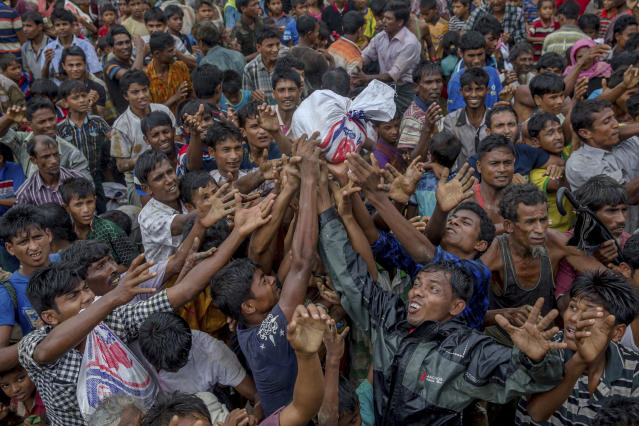 <p>Rohingya Muslims, who crossed over from Myanmar into Bangladesh, stretch their arms out to collect food items distributed by aid agencies near Balukhali refugee camp, Bangladesh, Monday, Sept. 18, 2017. (Photo: Dar Yasin/AP) </p>