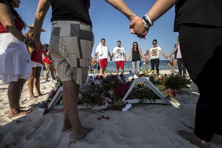People hold hands as they pray in a circle around bouquets of flowers laid in tribute on the beach of the Imperial Marhaba resort, which was attacked by a gunman, in Sousse, Tunisia