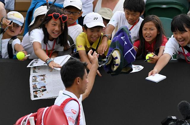 National hero: Kei Nishikori throws his towel towards young fans as he leaves the court after beating Ernests Gulbis (AFP Photo/Glyn KIRK)