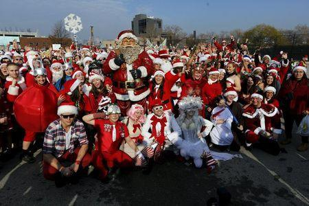 Revelers dressed in Santa Claus and other holiday themed outfits pose for a group photo before the start of the annual SantaCon event in the Brooklyn borough of New York, December 12, 2015. REUTERS/Brendan McDermid
