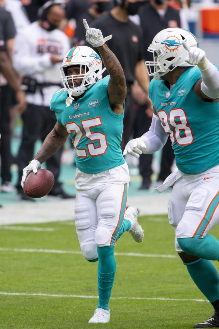 FILE - Miami Dolphins cornerback Xavien Howard (25) points to the sky as he celebrates intercepting a pass intended for Cincinnati Bengals wide receiver Tyler Boyd (not shown) along with Miami Dolphins defensive tackle Raekwon Davis (98) during an NFL football game in Miami Gardens, Fla., in this Sunday, Dec. 6, 2020, file photo. All-Pro cornerback and reigning NFL interception leader Xavien Howard wants a new contract from the Miami Dolphins, and there is no guarantee he will attend the three-day mandatory minicamp starting Tuesday, June 15, 2021. (AP Photo/Doug Murray, File)