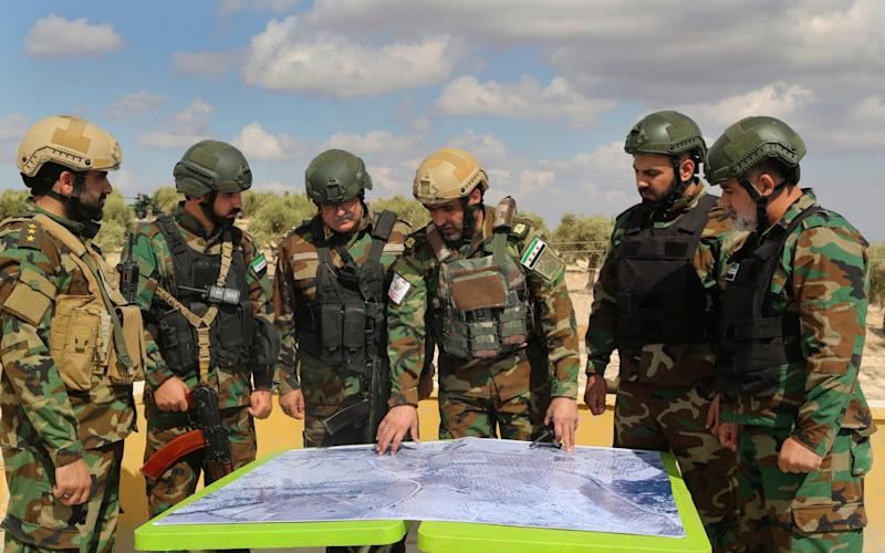 Turkish-backed forces from the Free Syrian Army look at a map during military maneuvers - AP