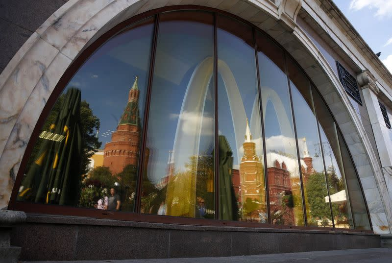 The walls and towers of the Kremlin are reflected in a window of a closed McDonald's restaurant, one of four temporarily closed by the state food safety watchdog, in Moscow