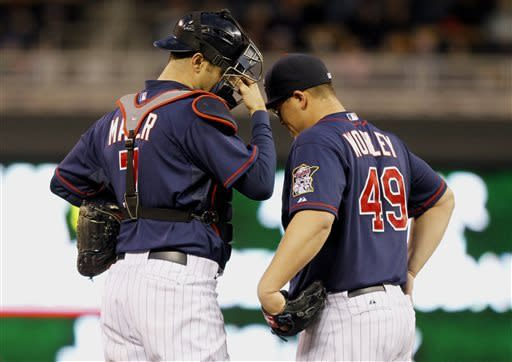 Minnesota Twins starting pitcher Vance Worley (49) talks with catcher Joe Mauer (7) during the fourth inning of a baseball game against the Texas Rangers, Thursday, April 25, 2013, in Minneapolis. (AP Photo/Genevieve Ross)