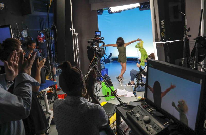 """This Aug. 6, 2019 photo shows production members clapping for Salia Woodbury, 10, left, from Irvine, Calif., on the set with """"Sesame Street"""" muppet Karli and puppeteer Haley Jenkins during a taping about parental addiction in New York. Sesame Workshop is addressing the issue of addiction. Data shows 5.7 million children under 11 live in households with a parent with substance use disorder. Salia's parents are in recovery after struggling with addiction and share her experience with the show's Karli—whose muppet character has a mom who is also in recovery. (AP Photo/Bebeto Matthews)"""