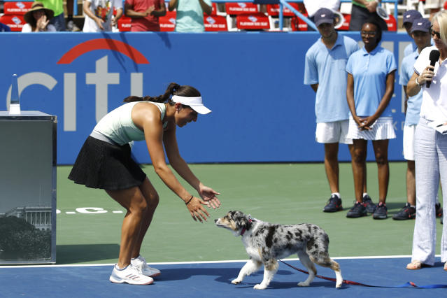 Jessica Pegula , left,greets her dog Maddie during a victory ceremony after defeating Camila Giorgi, of Italy, in a final match at the Citi Open tennis tournament, Sunday, Aug. 4, 2019, in Washington. (AP Photo/Patrick Semansky)