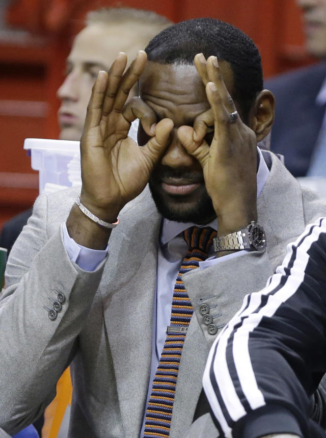 Miami Heat's LeBron James makes a face as he sits on the bench during the first half of an NBA basketball game against the Chicago Bulls, Sunday, Feb. 23, 2014, in Miami. James did not play as he is recovering from a broken nose. (AP Photo/Lynne Sladky)