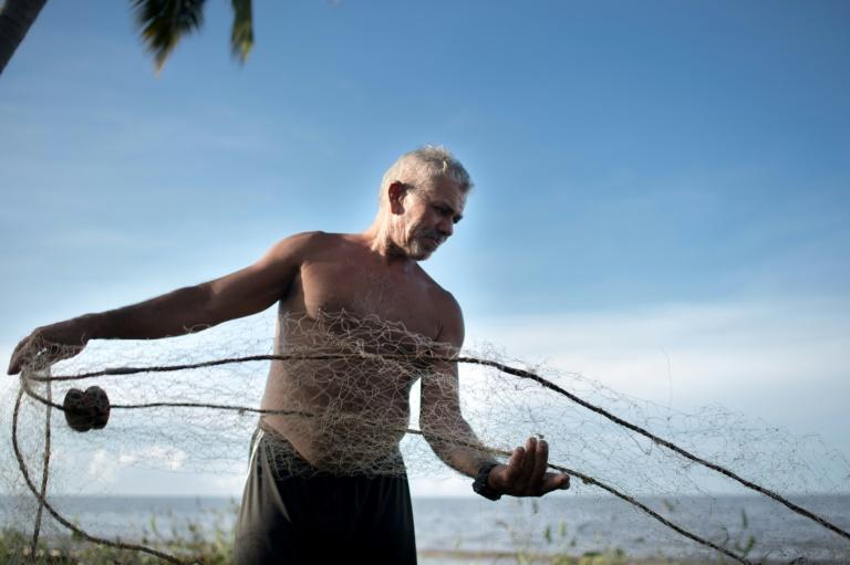 A fisherman prepares his net at Lake Maracaibo, Venezuela where an eight-year economic crisis has left people with shortages of food and fuel despite the country sitting on massive oil reserves (AFP/Federico PARRA)