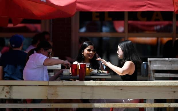 Patrons have a meal at a patio in the Byward Market in Ottawa on Saturday, June 12, 2021. Patios reopened across the province this weekend after being closed for two months due to public health restrictions. (Justin Tang/The Canadian Press - image credit)