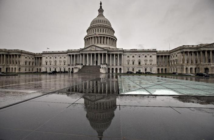 """In this Oct. 7, 2013, photo. the U.S. Capitol is reflected during rain in Washington. Americans are finding little they like about President Barack Obama or either political party, according to a new poll that suggests the possibility of a """"throw the bums out"""" mentality in next year's midterm elections. (AP Photo/J. Scott Applewhite)"""