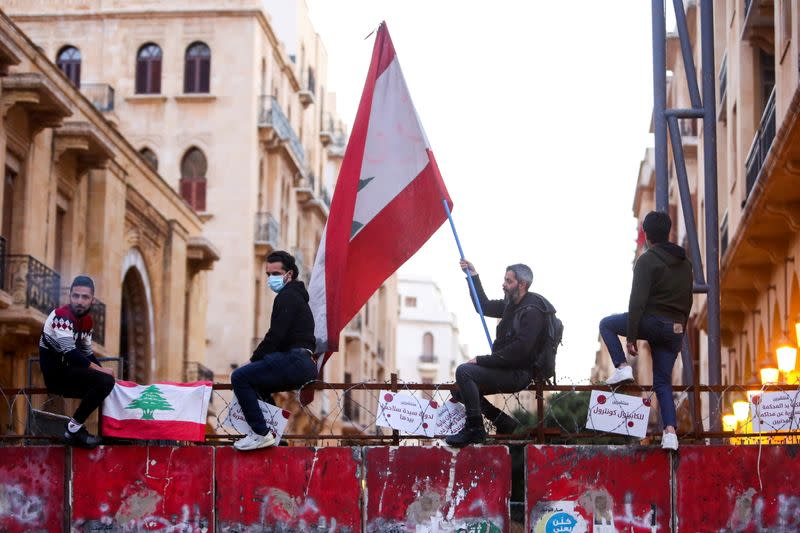 FILE PHOTO: A demonstrator holds a Lebanese flag during a protest against the fall in Lebanese pound currency and mounting economic hardships, in Beirut, Lebanon March 12, 2021