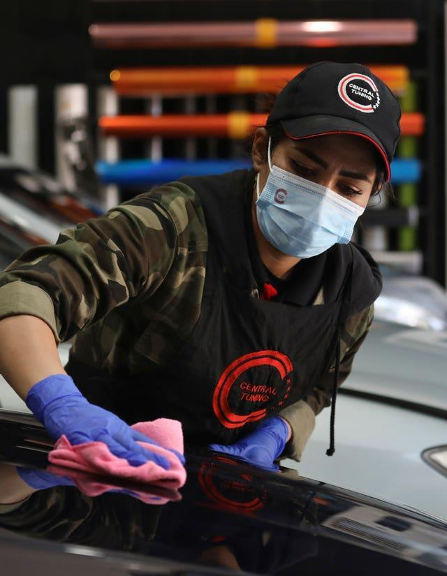 Female Iranian car detailer Maryam Roohani polishes a car at a detailing shop in Tehran