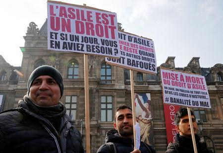 """Migrants hold placards which read """"Asylum is a right. And if one day you need it ?"""" and """"Death of the right to asylum"""" during a demonstration against a new """"migration-asylum bill"""" by French government in Paris, France February 21, 2018.  REUTERS/Pascal Rossignol"""