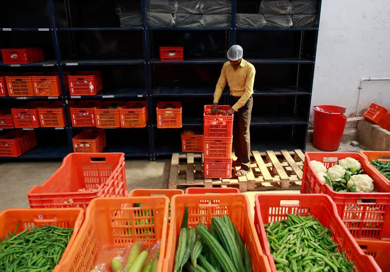An employee sorts out vegetables before packing them at a Big Basket warehouse on the outskirts of Mumbai