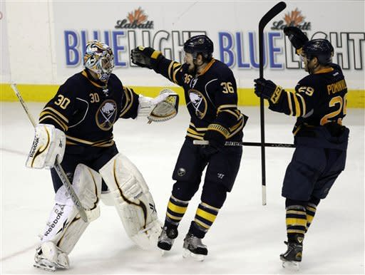 Buffalo Sabres goalie Ryan Miller celebrates their 2-1 shootout win over the Boston Bruins with Patrick Kaleta (36) and Jason Pominville (29) in an NHL hockey game in Buffalo, N.Y., Friday, Feb. 24, 2012. (AP Photo/David Duprey)