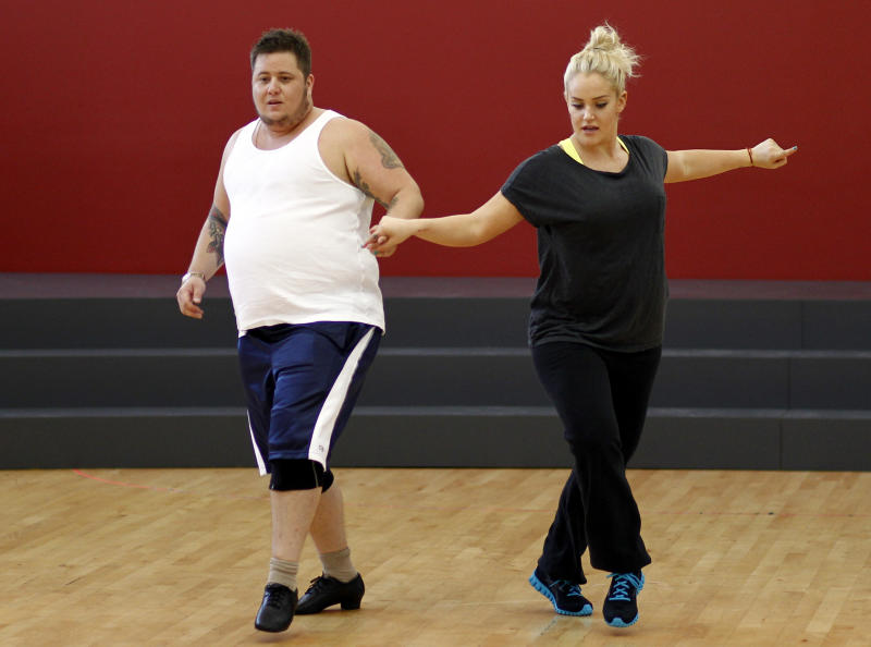 """Chaz Bono, left, and Lacey Schwimmer practice dance steps while rehearsing for the upcoming season of """"Dancing of the Stars"""" in Los Angeles, Wednesday, Sept. 7, 2011.   The new season of """"Dancing with the Stars"""" premieres Sept. 19 on ABC. (AP Photo/Matt Sayles)"""
