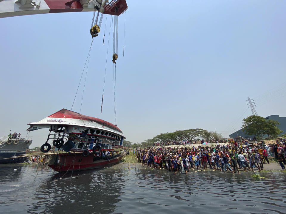 Rescuers pull out a ferry that sank Sunday night after being hit by a cargo vessel in the Shitalakkhya River in Narayanganj district, outside Dhaka, Bangladesh, Monday, April 5, 2021. 25 bodies were recovered as on Monday. (AP Photo/Mushfiqul Alam)