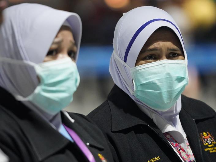 Health officials wear face masks at an inspection site at the Kuala Lumpur International Airport in Sepang, Malaysia, Tuesday, Jan. 21, 2020. Countries both in the Asia-Pacific and elsewhere have initiated body temperature checks at airports, railway stations and along highways in hopes of catching those at risk of carrying a new coronavirus that has sickened more than 200 people in China. (AP Photo/Vincent Thian)