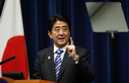 Japan's PM Abe looks at a prompter as he speaks during a news conference to wrap up the ASEAN-Japan Commemorative Summit Meeting at his official residence in Tokyo