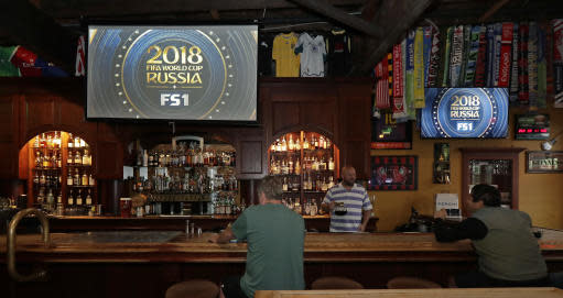 Russ Heaton, second from right, owner of Doyle's Public House in Tacoma, Wash., serves coffee to customers during halftime of a World Cup soccer match between Brazil and Costa Rica that began at 5:00 AM, PDT. Friday, June 22, 2018. Despite Team USA not making it to the World Cup, Heaton says his pub will show every minute of every World Cup match live. (AP Photo/Ted S. Warren)