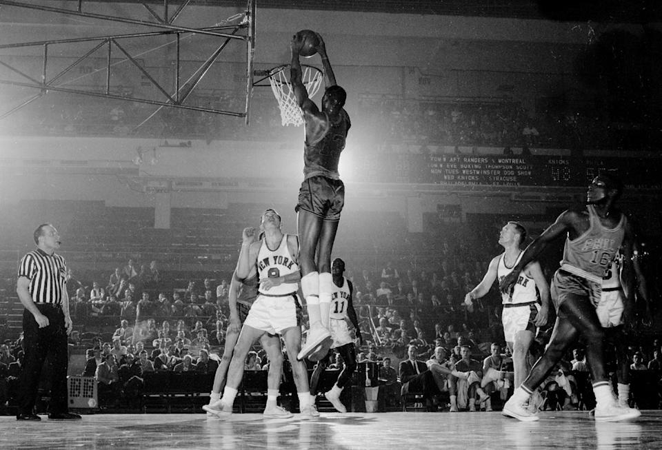 Wilt Chamberlain stretches and dunks two points as Phil Jordon and Johnny Green of the Knicks watch helplessly. (Charles Hoff/NY Daily News Archive via Getty Images)