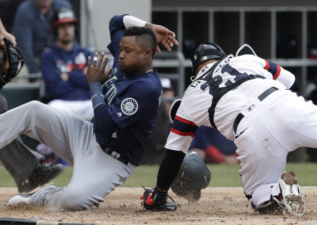 Seattle Mariners' Tim Beckham, left, scores on a three-run double by Daniel Vogelbach as Chicago White Sox catcher Welington Castillo misses the ball during the third inning of a baseball game in Chicago, Sunday, April 7, 2019. (AP Photo/Nam Y. Huh)