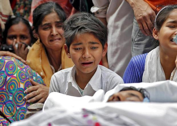 People mourn next to the body of Muddasir Khan, who was wounded on Tuesday in a clash between people demonstrating for and against a new citizenship law, after he succumbed to his injuries, in a riot affected area in New Delhi