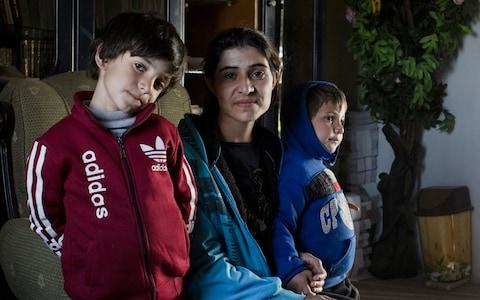 Barfe Khalaf Farho, 26, a Yazidi from Sinjar in Iraq, is photographed withe her two sons Jegar, five and Jan, three, in a Yazidi cultural centre in Hassakeh Province - Credit: Sam Tarling for The Telegraph