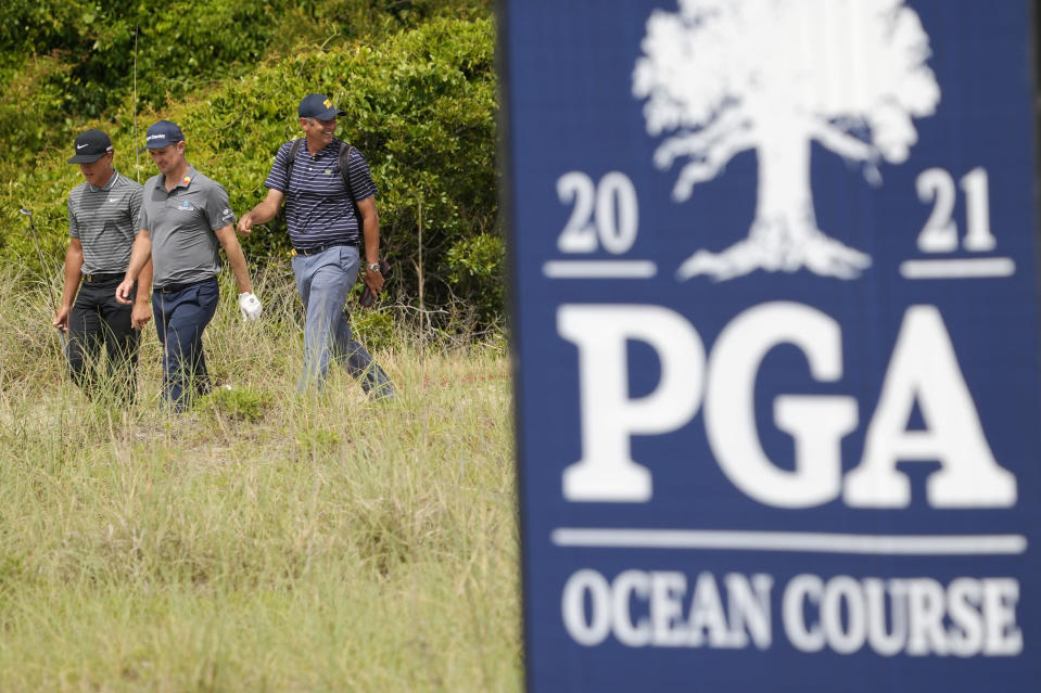Justin Rose, left, of England, and Cameron Champ, middle, walk to the 14th green during a practice round at the PGA Championship golf tournament on the Ocean Course Wednesday, May 19, 2021, in Kiawah Island, S.C. (AP Photo/David J. Phillip)