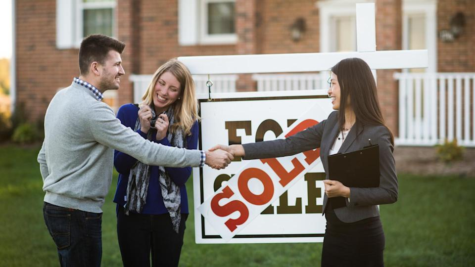 happy couple standing next to for sale sign shaking hands with real estate agent