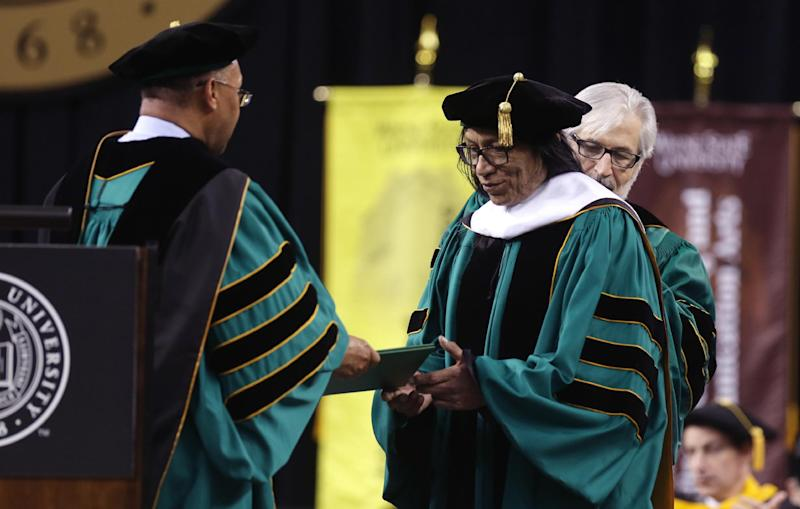 """Wayne State University Board of Governors Vice Chair Gary Pollard, left, presents a Doctor of Humane Letters honorary degree to Sixto Rodriguez, Thursday, May 9, 2013 in Detroit, during the university's commencement. Rodriguez's two albums in the early 1970s received little attention in the United States but he unknowingly developed a cult following in South Africa during the apartheid era. He was the subject of an Oscar-winning documentary, """"Searching for Sugar Man."""".(AP Photo/Carlos Osorio)"""