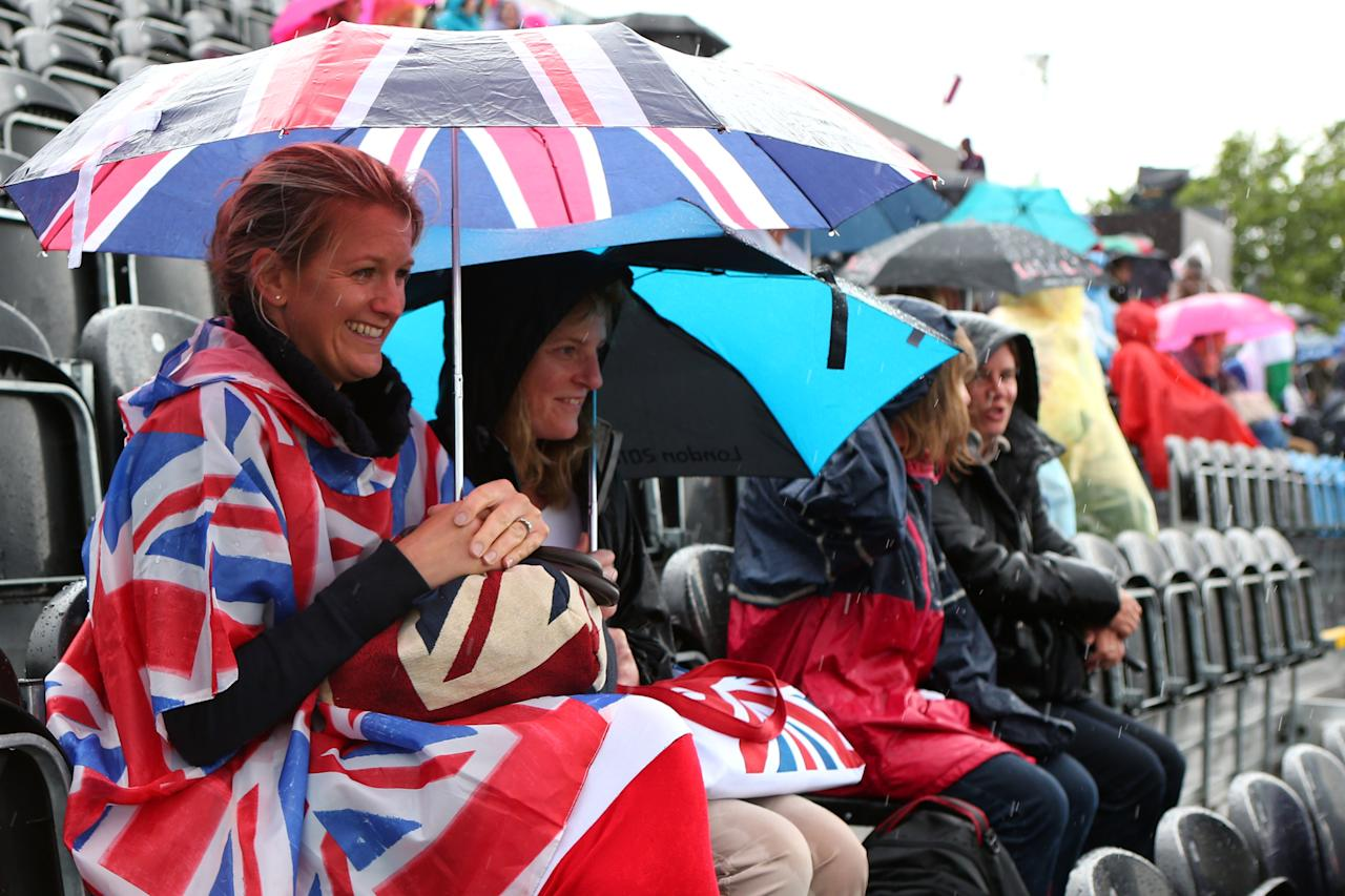 LONDON, ENGLAND - JULY 29:  Equestrian fans shield themselves from the rain on Day 2 of the London 2012 Olympic Games at Greenwich Park on July 29, 2012 in London, England.  (Photo by Alex Livesey/Getty Images)