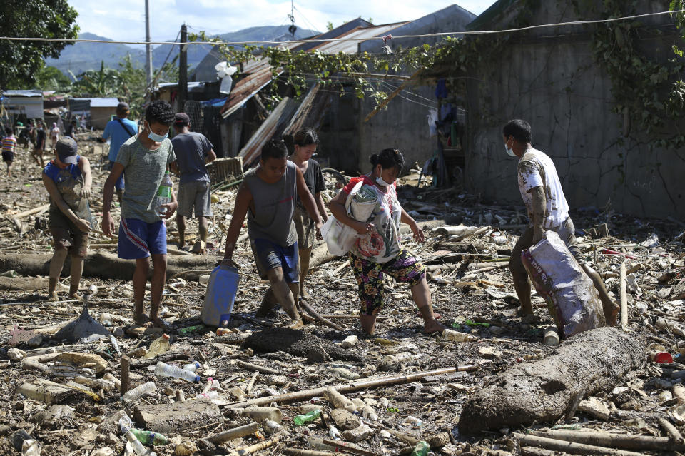 Residents walk through mud and debris at the typhoon-damaged Kasiglahan village in Rodriguez, Rizal province, Philippines on Friday, Nov. 13, 2020. Thick mud and debris coated many villages around the Philippine capital Friday after Typhoon Vamco caused extensive flooding that sent residents fleeing to their roofs and killing dozens of people. (AP Photo/Aaron Favila)